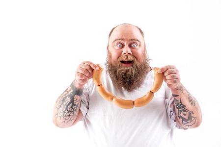 Photo pour Happy fat man eating meat with enjoyment - image libre de droit
