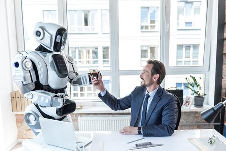Foto de Caring robot is giving espresso to businessman - Imagen libre de derechos