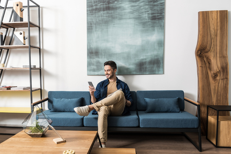 Photo pour Happy youthful guy bearded resting with cellphone in living room - image libre de droit