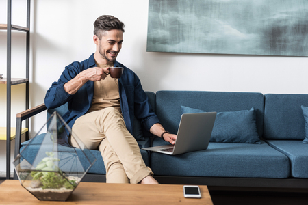 Foto de Happy youthful guy browsing internet via notebook in living room - Imagen libre de derechos