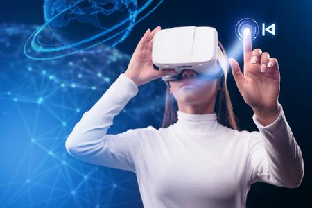 Foto de Serious young woman using virtual reality device - Imagen libre de derechos