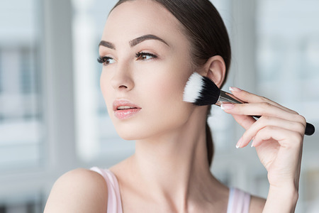Photo pour Serious attractive woman applying visage cosmetics - image libre de droit