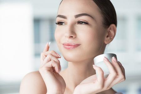 Photo pour Happy woman using visage cosmetics - image libre de droit