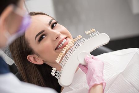 Foto de Physician enclosing dental crown to happy lady - Imagen libre de derechos