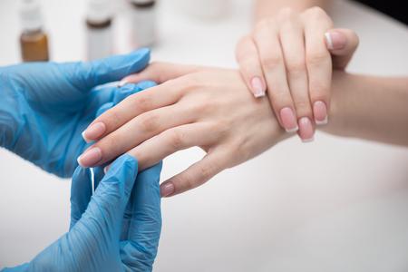 Foto de Manicurist is wiping oil in cuticle of young woman - Imagen libre de derechos