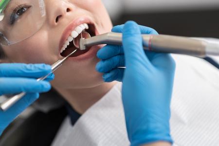 Foto de Dentist curing oral cavity of cheerful woman - Imagen libre de derechos
