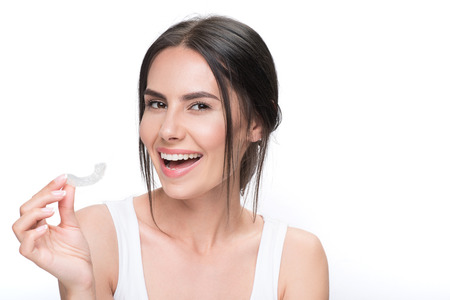 Photo pour Cheerful young woman showing clear aligner - image libre de droit