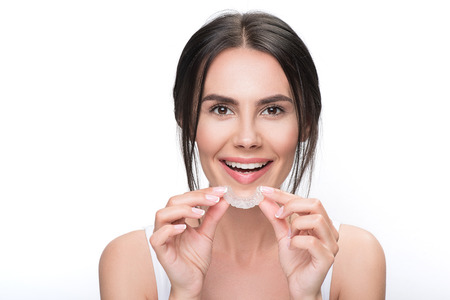 Photo for Excited young woman holding clear aligner - Royalty Free Image