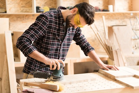 Photo for Attractive energetic carpenter is standing at his job - Royalty Free Image