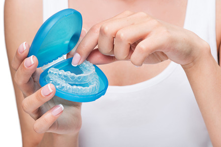 Foto de Young woman holding cover with clear aligners - Imagen libre de derechos