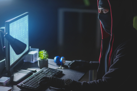 Photo pour Poor protection system. Profile of concentrated computer burglar in mask is downloading private information while sitting at table - image libre de droit