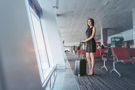 Foto de Attractive business woman is waiting for her flight with smile - Imagen libre de derechos