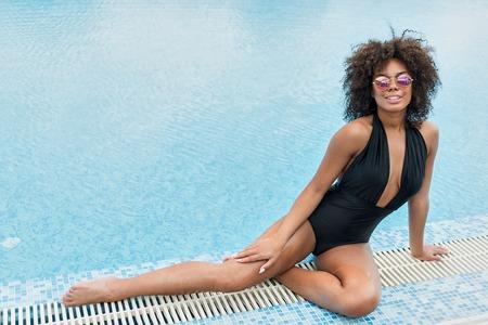 Photo pour Cheery young mulatto woman recreating near water - image libre de droit