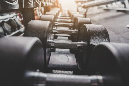 Photo pour Iron dumbbells locating in row on shelves - image libre de droit