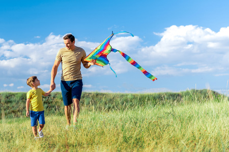 Photo for Happy father and son playing with kite in nature - Royalty Free Image