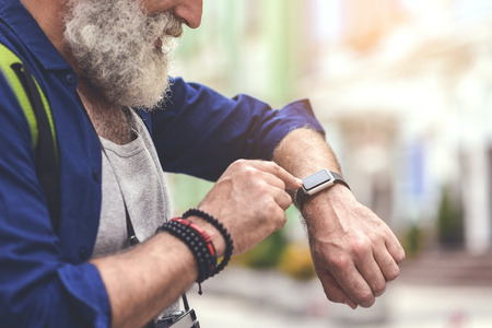 Foto per Cheerful old man touching screen of his watch - Immagine Royalty Free