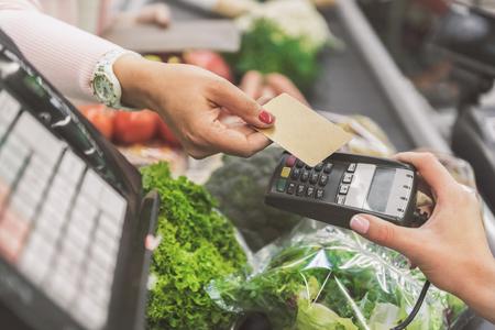 Photo pour Buyer giving plastic card to cashier - image libre de droit