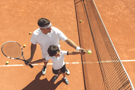Photo pour Family learning to play tennis - image libre de droit