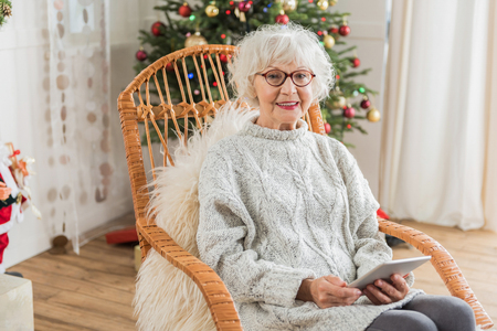 Photo pour Technological device. Portrait of delightful mature lady is holding tablet while looking at camera with joy. She is sitting in cozy chair with Christmas tree on background - image libre de droit