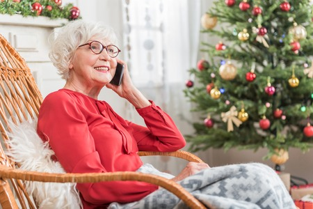 Foto de Enjoying conversation. Charming senior woman is talking on mobile phone and expressing happiness. She is sitting in rocking chair against Christmas tree. Copy space in the right side - Imagen libre de derechos