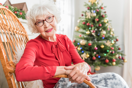 Foto de Great mood. Portrait of charming elderly woman is sitting in rocking chair and looking at camera with smile. She is resting with Christmas tree on background. Copy space in the right side - Imagen libre de derechos