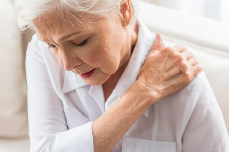 Photo pour Unpleasant feeling. Old cheerless gray-haired woman is touching her neck with closed eyes while expressing strong pain - image libre de droit