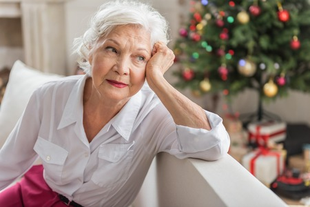 Photo pour Nostalgic memories. Melancholic aged lady is looking aside thoughtfully while leaning on elbow and touching her face. She is resting on couch with Christmas tree and gift boxes on background - image libre de droit