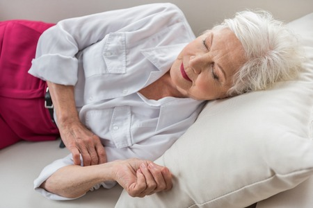 Foto de Need to rest. Stylish elegant aged lady is dozing on white couch at her home - Imagen libre de derechos
