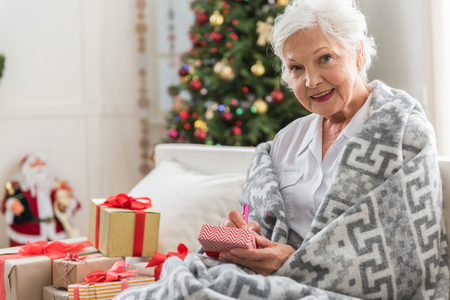 Foto de Preparing gifts. Portrait of charming aged woman is sitting on couch among presents and writing wishes. She is looking at camera with joy with Christmas tree on background. Copy space in the left side - Imagen libre de derechos