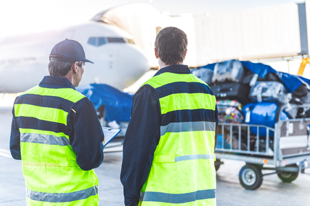 Photo for Workers controlling luggage in airdrome - Royalty Free Image
