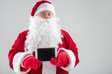 Photo pour Generous Father Frost showing modern gadget - image libre de droit