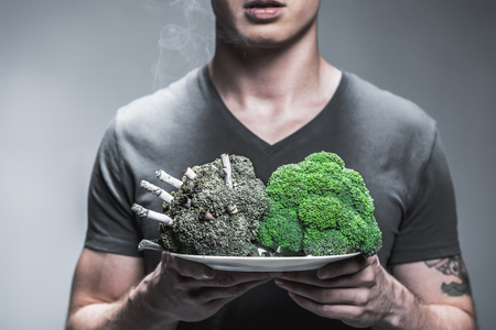 Photo pour Nicotine is toxic for your health. Close up of arms of young man showing the difference between lungs of smoker and average person. Focus on green fresh broccoli and spoiled one with cigarettes on plate - image libre de droit