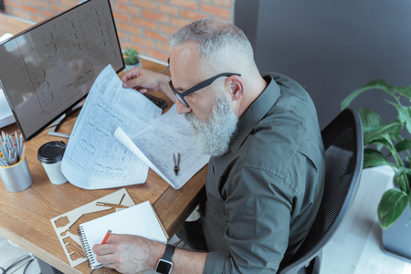Foto de Serious elderly engineer is writing in notepad - Imagen libre de derechos