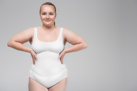 Photo for Cheerful chubby young woman is satisfied with her figure - Royalty Free Image