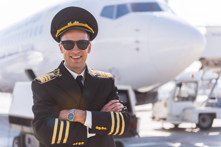 Photo pour Hilarious smiling aviator locating near plane - image libre de droit
