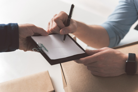 Foto de Confirmation. Close-up top view of hand of professional courier is holding folder while recipient male is signing invoice and accepting delivery of box - Imagen libre de derechos