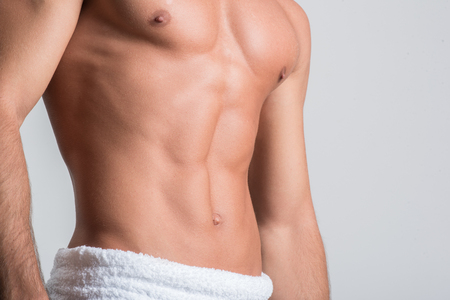 Foto de Manly and muscular. Close-up of trained torso of young man with towel on his hips. He is standing isolated. Health and beauty concept - Imagen libre de derechos