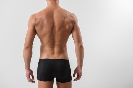 Photo for Satin perfection of skin. Close-up of back of confident young sportsman is standing in black underwear. He is showing his trained muscular body. Isolated and copy space in right side - Royalty Free Image