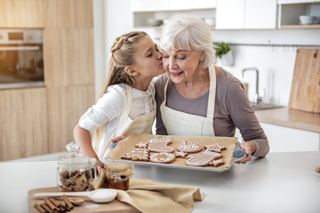 Photo for Happy child thanking grandma for sweet pastry - Royalty Free Image