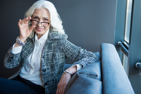 Foto de Positive senior elegant businesswoman is sitting on sofa - Imagen libre de derechos