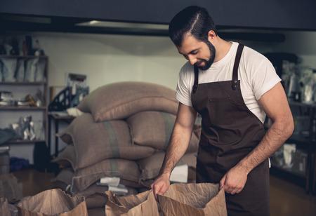Foto de Side view happy unshaven young master keeping sack. He looking at coffee beans. Work concept - Imagen libre de derechos