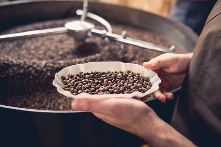 Foto de Close up professional coffee roaster holding bowl with beans. Control concept - Imagen libre de derechos
