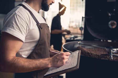 Foto de Serene bearded man writing information about roasting beans in cooler cylinder of special machine. Industry concept - Imagen libre de derechos