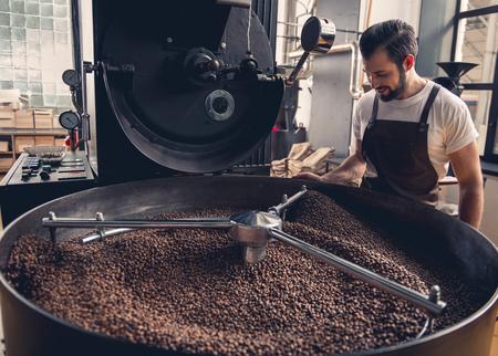 Foto de Side view smiling unshaven worker watching at coffee beans situating in grain chiller. Industry concept - Imagen libre de derechos