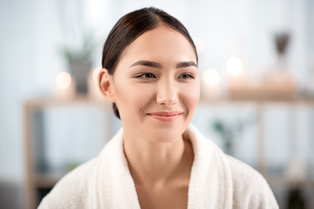 Photo pour Happy mood. Portrait of cheerful mysterious young asian girl in terry bathrobe is spending time in beauty salon. She is looking aside with smile while resting with pleasure - image libre de droit