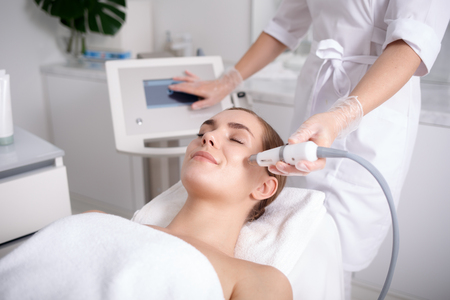 Foto de Side view of happy young woman getting cavitation rejuvenating skin treatment at spa. She is lying on massage table and smiling. Beautician is touching monitor screen while holding tool near female cheek - Imagen libre de derechos