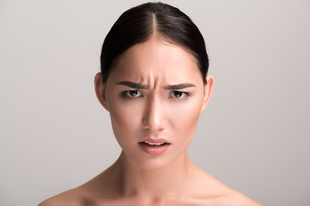 Foto de Full of rage. Close-up portrait of young angry asian woman is looking at camera with annoyance while frowning her forehead. Isolated background - Imagen libre de derechos