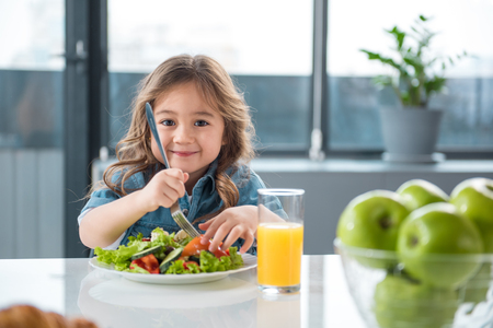 Foto de Portrait of pretty little female child having healthy breakfast. She is holding fork under the chopped vegetables and smiling - Imagen libre de derechos