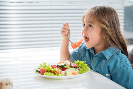 Photo pour Side view of hungry asian girl eating piece of tomato with appetite. She is sitting at table in kitchen - image libre de droit