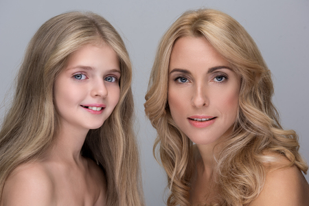 Foto de My pride. Portrait of optimistic attractive elegant mother and adorable little daughter are standing with naked shoulders while looking at camera with joy. Isolated background - Imagen libre de derechos